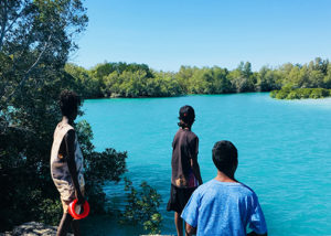 3 young males from broome standing on rocks looking out at water