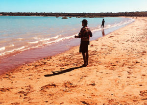 teenage male from youth justice program stands on the beach fishing in broome