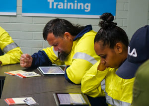 one male and female jobseeker in high vis working on ipads in front of sign that says training