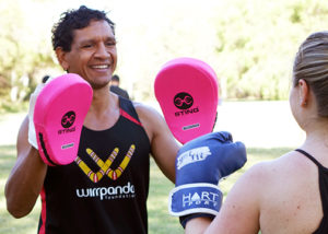 troy cook in wirrpanda foundation uniform holding boxing pads smiling