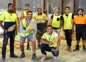 group of adult men in work wear at brick laying training course smiling at camera