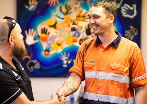 2 men standing smiling and shaking hands in front of aboriginal art