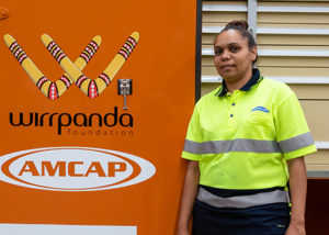 successful female jobseeker in high vis stands infront of wirrpanda foundation and amcap logo sign