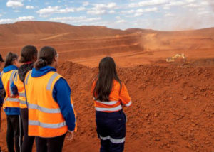 group of women in high vis on red dirt mine site watching dig