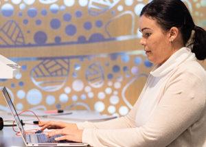 wirrpanda foundation staff member working on laptop in front of aboriginal art mural