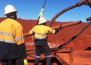 2 mining workers on red dirt site lifting piping