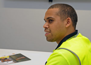 indigenous man at an office desk in high vis