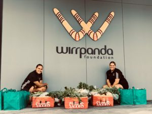 emily and jacinta of the wirrpanda foundation with donation food boxes in front of wirrpanda foundation logo