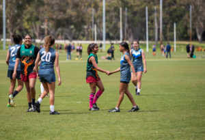 group of girls playing afl football shaking hands