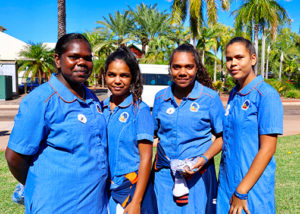 four female high school students in their uniform standing in front of palm trees in broome