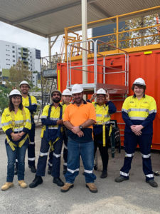 a group of people in high vis and hard hats smiling at camera