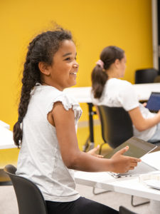 female child smiling and playing on laptop
