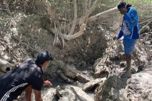 indigenous boy and mentor in full circle partnership program standing on rocks spear fishing