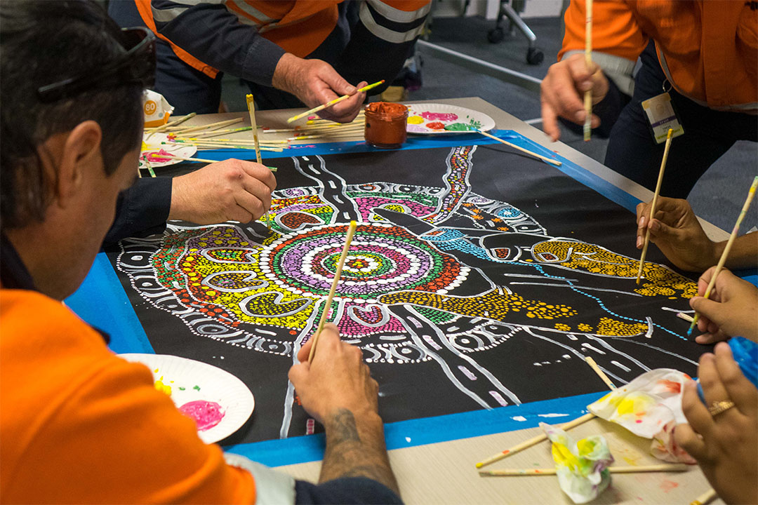 group of people painting aboriginal art
